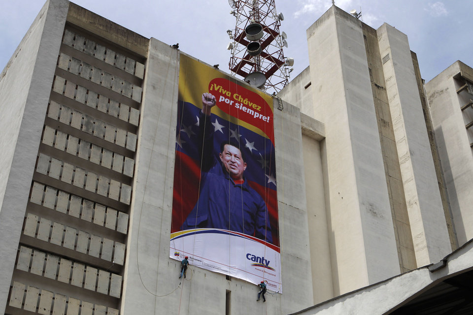 FILE - In this March 7, 2013 file photo, workers of the state-owned telephone company Cantv hang a banner honoring Venezuela\'s late President Hugo Chavez on the building housing the company\'s administrative offices, in Caracas, Venezuela. Politics rule everyday government in Venezuela, from state oil company to subways. State companies such as oil producer PDVSA and the manager of Caracas\' subway system used to be known around the world for their professionalism. In recent years, many of those companies have seen service and revenue deteriorate as political cadres rather than engineers were brought in to run everything from oil exploration to mass transit. (AP Photo/Esteban Felix, File)