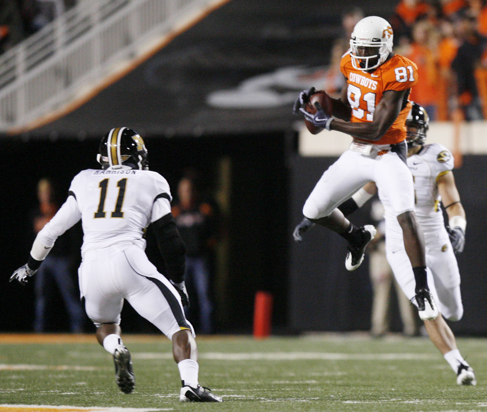 Photo - Justin Blackmon catches a pass between Jarrell Harrison (11) and Andrew Gachkar (6) during the college football game between Oklahoma State University (OSU) and the University of Missouri (MU) at Boone Pickens Stadium in Stillwater, Okla. Saturday, Oct. 17, 2009.  Photo by Sarah Phipps, The Oklahoman