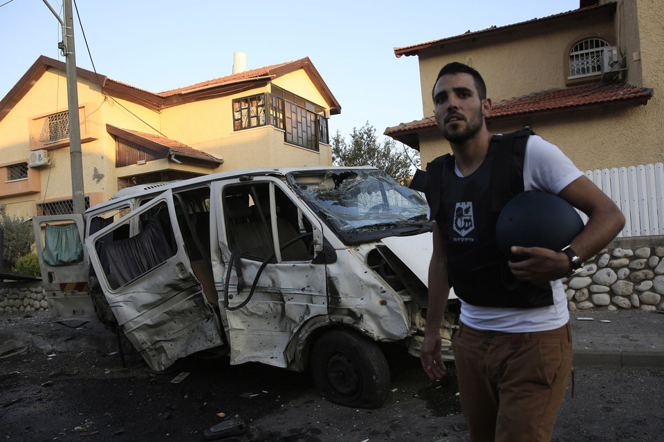 Photo - A man stands in front of a van damaged from a rocket fired from Gaza which landed in the middle of a residential neighborhood in the southern city of Kiryat Gat, Israel, Thursday, July 31, 2014. An Israeli was seriously wounded when a Palestinian rocket exploded in a residential area of the city. Another rocket was intercepted over Tel Aviv by Israel's rocket defense system. Israeli attacks on Gaza continued today, killing many people as Prime Minister Benjamin Netanyahu vowed to destroy the Hamas tunnel network. (AP Photo/Tsafrir Abayov)