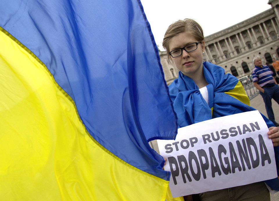 Photo - A demonstrator   behind an Ukrainian flag protests against Russian President Vladimir Putin on occasion of his visit to Austria  in front of Vienna's historic Hofburg palace  in Vienna  Tuesday June 24, 2014. Putin is on a one-day visit to Austria. (AP Photo/Herwig Prammer)