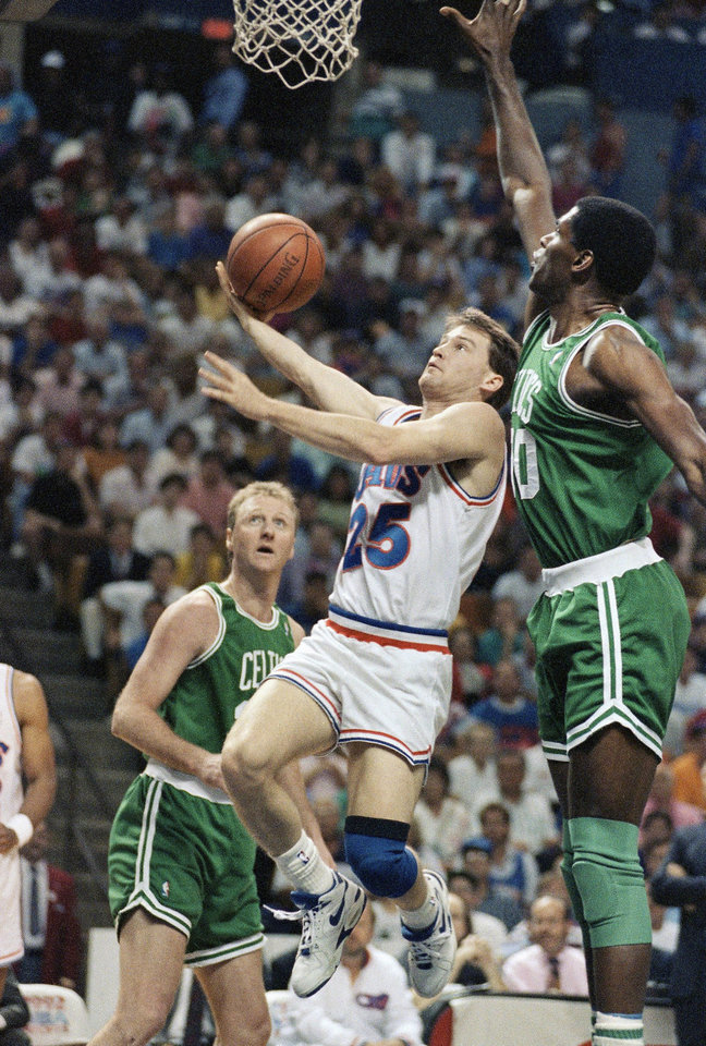 Photo - Cleveland Cavaliers guard Mark Price (25) drives inside Boston Celtics Robert Parish, right and Larry Bird, background, for a first quarter lay up during game seven of the NBA Eastern Conference Semifinal Game at the Richfield Coliseum, Sunday, May 17, 1992, Richfield, Ohio. (AP Photo/Mark Duncan)