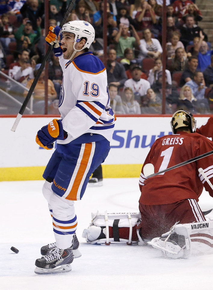 Photo - Edmonton Oilers' Justin Schultz (19) celebrates his goal against Phoenix Coyotes' Thomas Greiss (1), of Germany, during the first period of an NHL hockey game, Friday, April 4, 2014, in Glendale, Ariz. (AP Photo/Ross D. Franklin)