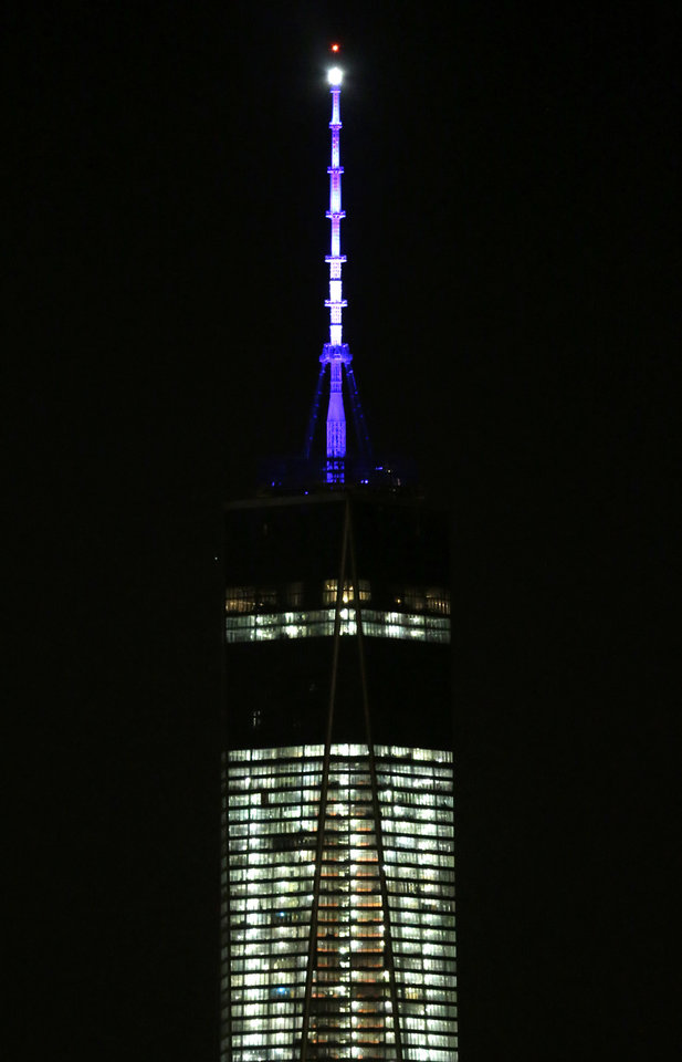 Photo - FILE - In this Nov. 8, 2013 file photo, the beacon and spire of 1 World Trade Center are lit up, as seen from The Heights neighborhood of Jersey City, N.J. The new World Trade Center tower in New York knocked Chicago's Willis Tower off its pedestal as the nation's tallest building when an international panel of architects announced Tuesday, Nov. 12, 2013 that the needle atop the skyscraper can be counted when measuring the structure's height.  (AP Photo/Julio Cortez, File)