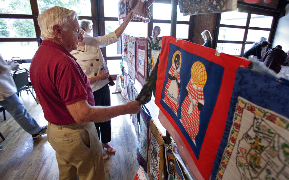 Photo - Above: Clarence Offen looks at a quilt offered for sale at a Mission Norman fundraiser last week.