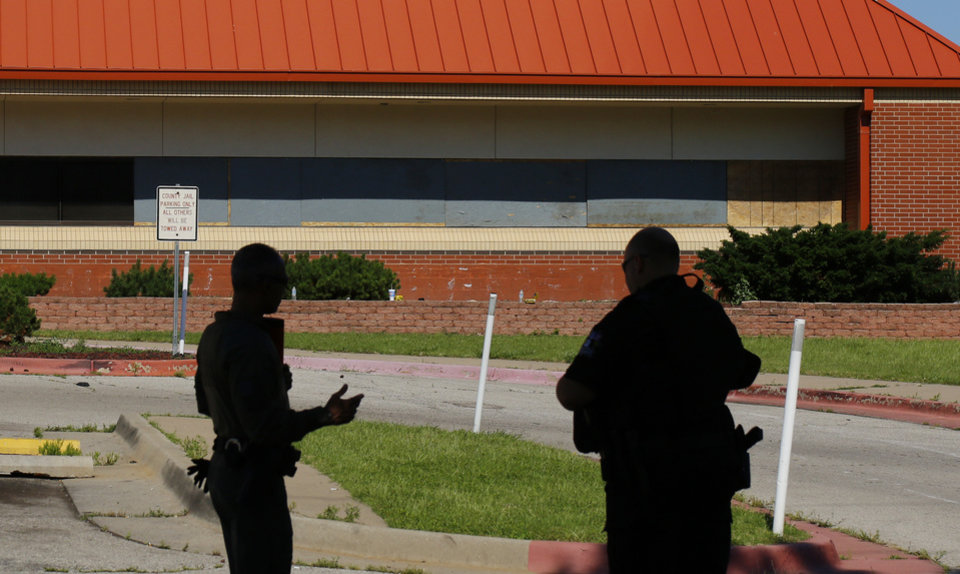 Photo - Deputies out front of the Oklahoma County Jail with boarded up windows in the background. Damage from Saturday night protest in downtown Oklahoma City, Sunday, May 31, 2020. [Doug Hoke/The Oklahoman]