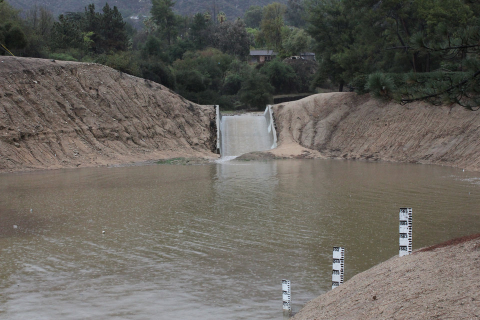 Photo - Storm water flows into a debris basin in Altadena, Calif., as thunderstorms dump rain on the San Gabriel Mountains on Saturday, March 1, 2014. Residents of some 1,200 homes in three foothill cities to the east were under evacuation orders due to danger of debris flows from steep slopes burned bare by recent wildfires. (AP Photo/ John Antczak)