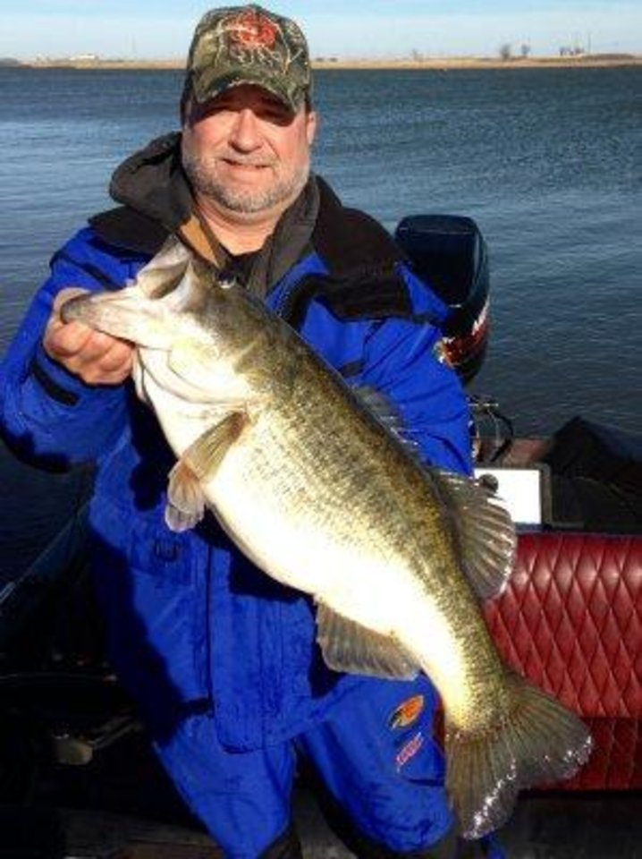 Photo -  Roger Robison of Skiatook caught the new lake record for largemouth bass at Sooner Lake on Jan. 12. The 11.4-pounder is now swimming in aquarium at the Bass  Pro Shop in Broken Arrow.