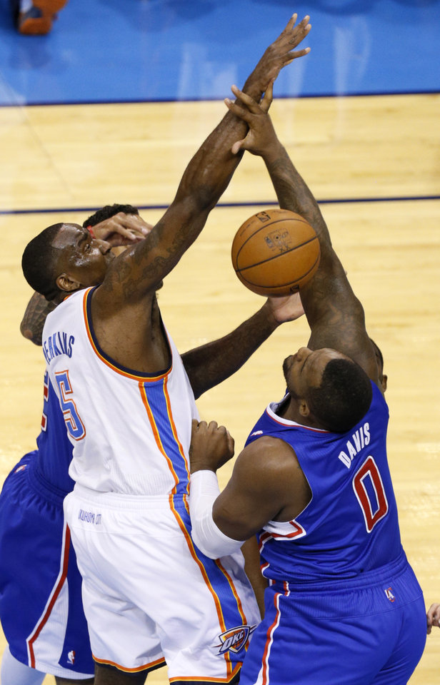 Photo - Oklahoma City's Kendrick Perkins (5) loses the ball beside Los Angeles' Glen Davis (0) during Game 5 of the Western Conference semifinals in the NBA playoffs between the Oklahoma City Thunder and the Los Angeles Clippers at Chesapeake Energy Arena in Oklahoma City, Tuesday, May 13, 2014. Photo by Bryan Terry, The Oklahoman