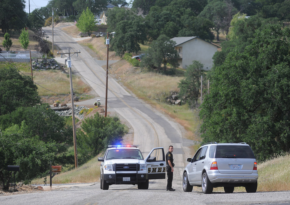 Photo - In a Sunday April 28, 2013 photo, a Calaveras County Sheriff's deputy detains a driver on Rippon Rd. in Valley Springs, Calif., where 8-year-old Leila Fowler was found murdered Saturday evening. (AP Photo/The Modesto Bee, Elias Funez) LOCAL TV OUT (KXTV10, KCRA3, KOVR13, FOX40, KMAX31, KQCA58, CENTRAL VALLEY TV); LOCAL PRINT OUT (TURLOCK JOURNAL, CERES COURIER, OAKDALE LEADER, MODESTO VIEW, PATTERSON IRRIGATOR, MANTECA BULLETIN, RIPON, RECROD, SONORA UNION DEMOCRAT, AMADOR LEDGER DISPATCH, ESCALON TIMES, CALAVERAS ENTERPRISE, RIVERBANKS NEWS) LOCAL INTERNET OUT (TURLOCK CITY NEWS.COM, MOTHER LODE.COM)