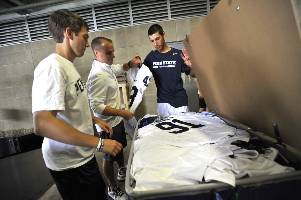 Photo - Penn State team managers Evan Tucker, left,  Jay Takach, center, and Nick Venturino  load equipment to be shipped to Ireland, in University Park, Pa., Tuesday, Aug. 26, 2014.   Penn State plays Central Florida in the Croke Park Classic, in Dublin, Ireland, this Saturday. (AP Photo/ Centre Daily Times, Nabil K. Mark) MANDATORY CREDIT; MAGS OUT