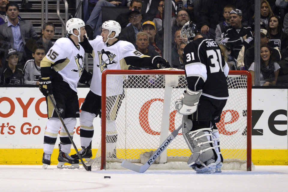 Photo - Pittsburgh Penguins left wing Tanner Glass, left, celebrates his goal with right wing Jayson Megna, center, as Los Angeles Kings goalie Martin Jones looks on during the second period of an NHL hockey game, Thursday, Jan. 30, 2014, in Los Angeles. (AP Photo)