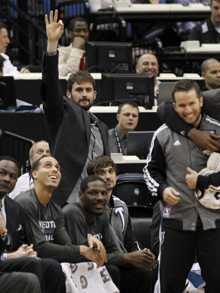 Photo - Minnesota Timberwolves forward Kevin Love cheers on his teammates from the bench during the first quarter of an NBA basketball game against the Houston Rockets in Minneapolis, Friday, April 11, 2014. Love was out with a hyper-extended right elbow. (AP Photo/Ann Heisenfelt)