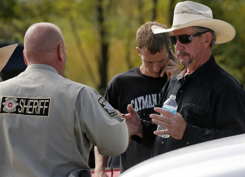 Photo - Tim Porter, right, talks with Beckham County Sheriff's Deputy J. Kessel, left, after giving a DNA sample at the scene where two cars were recovered from Foss Lake, in Foss, Okla., Wednesday, Sept. 18, 2013. Porter says he believes his grandfather's remains may be in one of the cars. The Oklahoma State Medical ExaminerÂ's Office says authorities have recovered skeletal remains of multiple bodies in the Oklahoma lake where the cars were recovered. (AP Photo/Sue Ogrocki) ORG XMIT: OKSO106