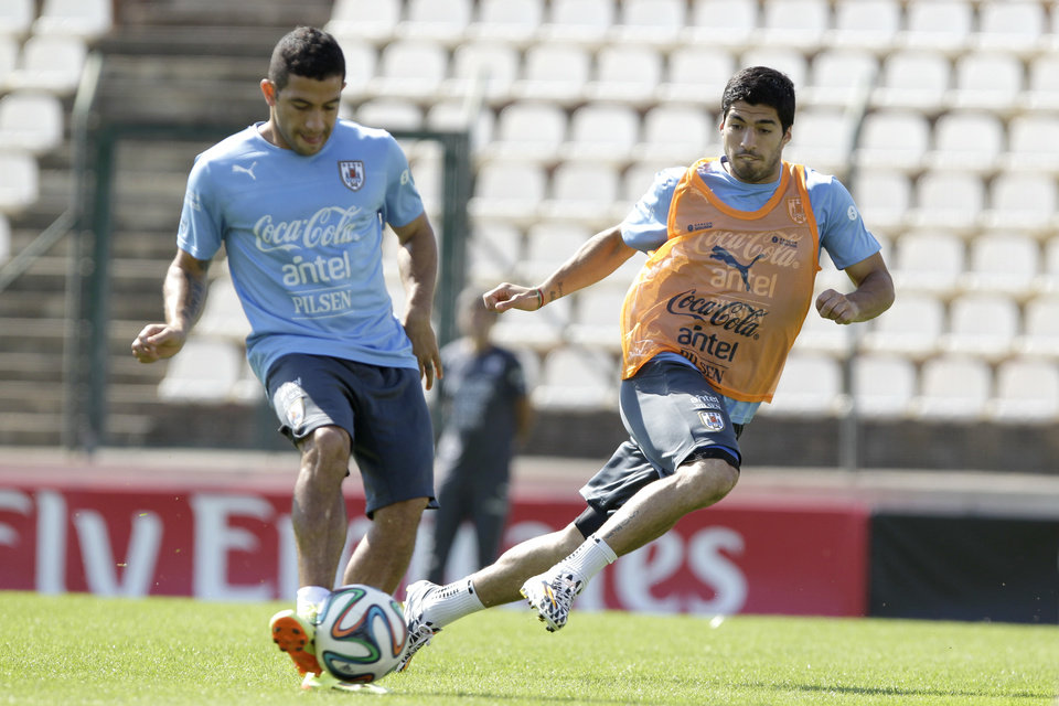Photo - Walter Gargano, left, and Luis Suarez, right, of a Uruguay's national team runs for the ball during a practice session at Arena do Jacare Stadium at the World Cup in Sete Lagoas, Brazil, Saturday, June 21, 2014. Uruguay plays in group D at the 2014 soccer World Cup. (AP Photo/Bruno Magalhaes)