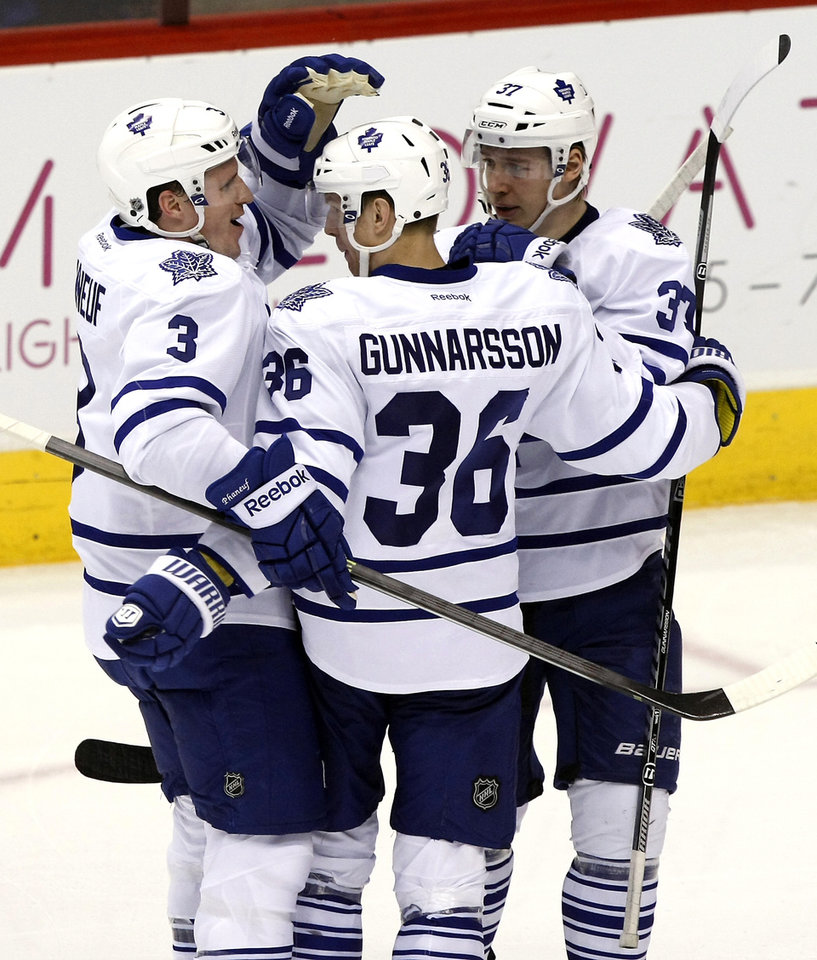 Photo - Toronto Maple Leafs defenseman Carl Gunnarsson (36) celebrates with Dion Phaneuf (3) and Carter Ashton (37) after scoring a second period goal against the Phoenix Coyotes during an NHL hockey game, Monday, Jan. 20, 2014, in Glendale, Ariz. (AP Photo/Rick Scuteri)