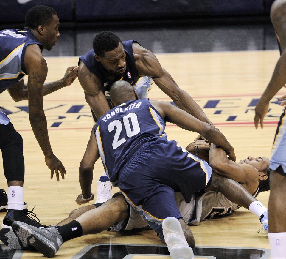 Photo - San Antonio Spurs' Kawhi Leonard, right, fights for a loose ball with Memphis Grizzlies' Quincy Pondexter (20), Tony Wroten, left, and Tony Allen during the second half of Game 1 of the Western Conference final NBA basketball playoff series Sunday, May 19, 2013, in San Antonio. San Antonio won 105-83. (AP Photo/Darren Abate)