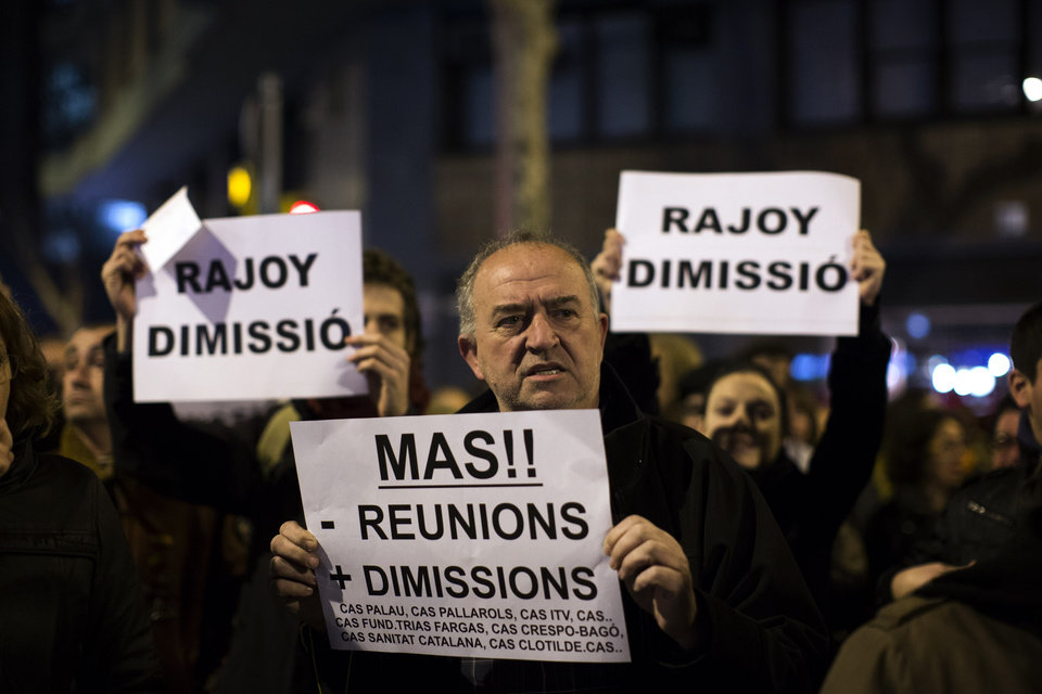 "Protesters carry banners reading: ""Rajoy and Mas resignation"" during a demonstration against corruption in front of the Popular Party offices in Barcelona, Saturday, Feb. 2, 2013. Spain's prime minister has denied media reports that allege he and members of his governing Popular Party accepted or made under-the-table payments.  Attorney General Eduardo Torres-Dulce said Friday there is sufficient cause to investigate allegations of irregular financing within Rajoy's party. Leading newspaper El Pais has published details of secret papers belonging to former party treasurer Luis Barcenas allegedly documenting undeclared payments. (AP Photo/Emilio Morenatti)"