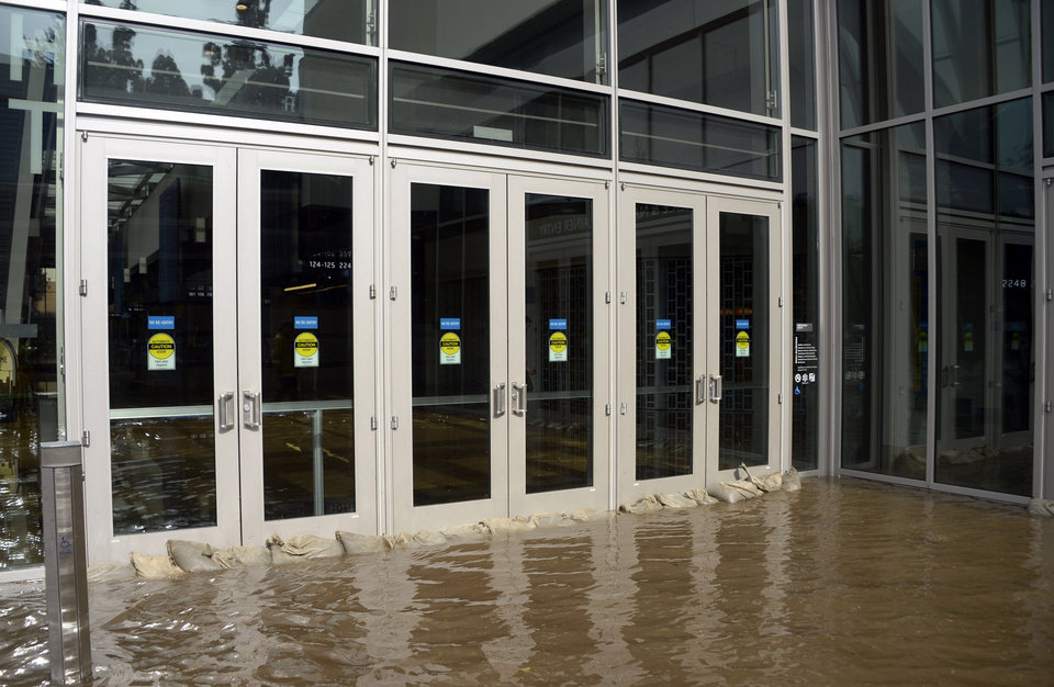 Photo - Sandbags fail to stop water from entering the main doors of Pauley Pavilion, home of UCLA basketball, on the UCLA campus after flooding from a broken 30-inch water main under nearby Sunset Boulevard inundated a large area of the campus in the Westwood section of Los Angeles, Tuesday, July 29, 2014.   The 30-inch (75-centimeter)  93-year-old pipe that broke made a raging river of the street and sent millions of gallons (liters) of water across the school's athletic facilities, including the famed floor of Pauley Pavilion, the neighboring Wooden Center and the Los Angeles Tennis Center, and a pair of parking structures that took the brunt of the damage. (AP Photo/Mike Meadows)