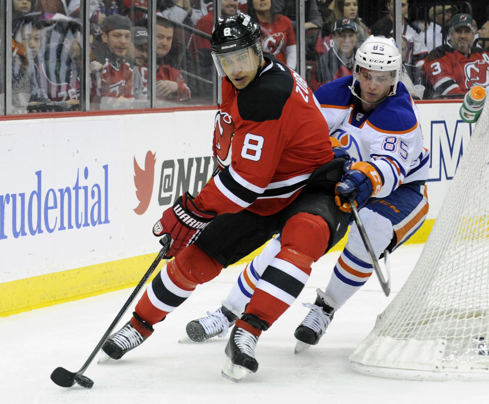 Photo - New Jersey Devils' Dainius Zubrus, left, skates with the puck as he is checked by Edmonton Oilers' Martin Marincin during the second period of an NHL hockey game, Friday, Feb. 7, 2014, in Newark, N.J. (AP Photo/Bill Kostroun)