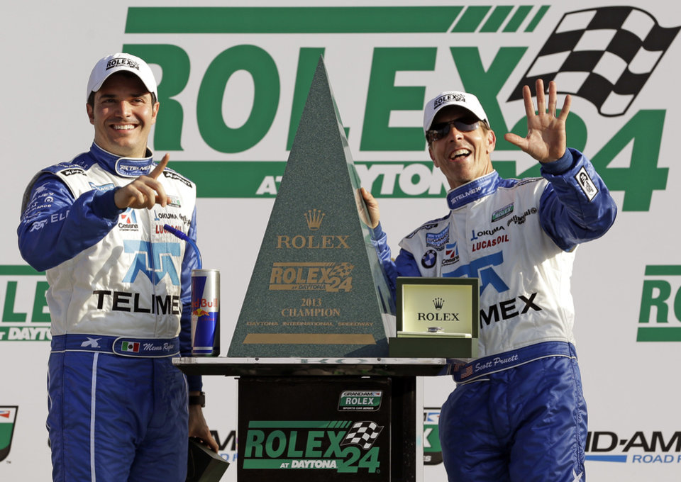 Driver's Memo Rojas, left, of Mexico, and Scott Pruett celebrate next to the championship trophy after winning Grand-Am Series Rolex 24 hour auto race at Daytona International Speedway, Sunday, Jan. 27, 2013, in Daytona Beach, Fla. (AP Photo/John Raoux)
