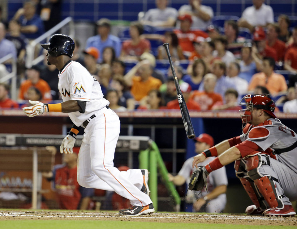 Photo - Miami Marlins' Adeiny Hechavarria, left, tosses his bat after hitting a triple to score Jarrod Saltalamacchia as St. Louis Cardinals catcher A.J. Pierzynski, right, looks on in the fourth inning during a baseball game, Monday, Aug. 11, 2014, in Miami. (AP Photo/Lynne Sladky)