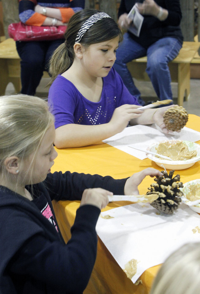 Photo - Sidney Freeny, 8, front, and Brooke Larue, 8, make bird feeders.