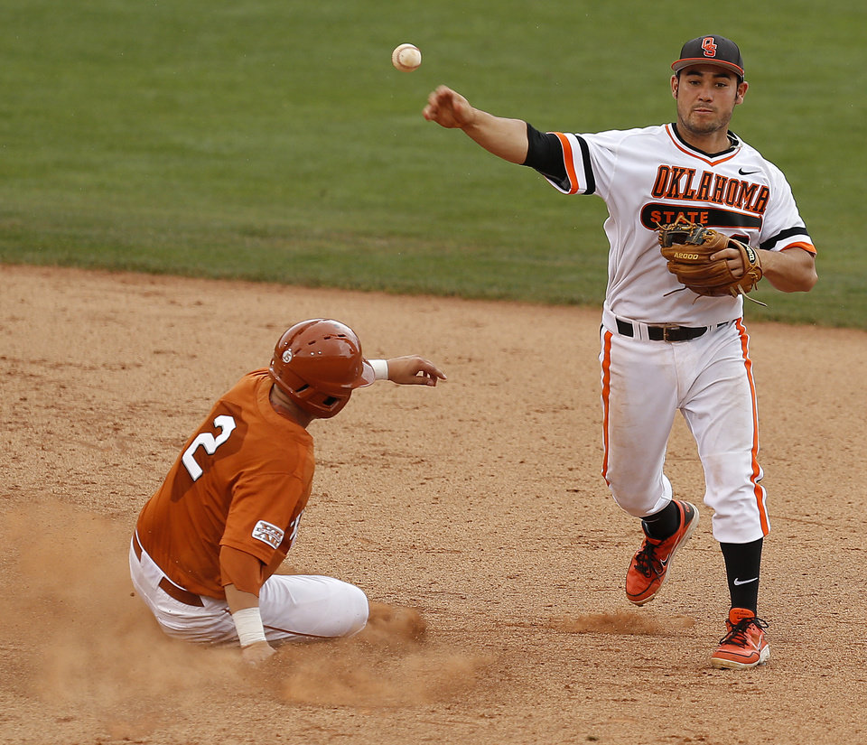 Photo - OSU's Tim Arakawa throws over Texas' Mark Payton for a double play in the third inning of a Big 12 Tournament baseball game between Oklahoma State University and the University of Texas at Chickasaw Bricktown Ballpark in Oklahoma City, Saturday, May 24, 2014. Photo by Bryan Terry The Oklahoman
