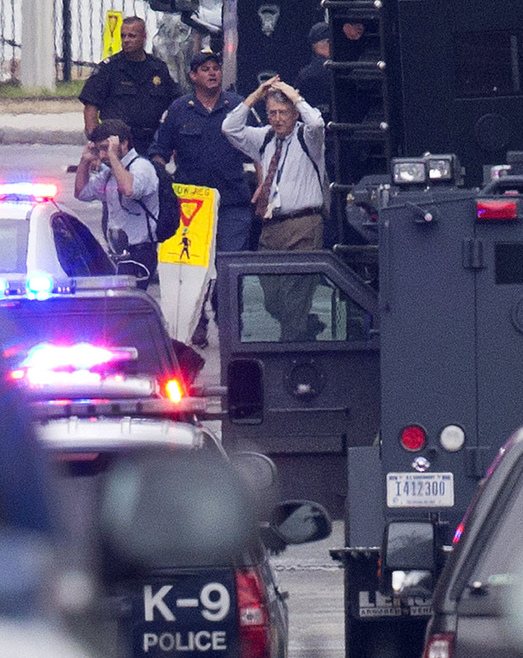 Photo - People hold their hands to their heads as they are escorted out of the building where a gunman was reported at the Washington Navy Yard in Washington, Monday, Sept. 16, 2013. A defense contractor went on a shooting rampage Monday inside a building at the heavily secured Washington Navy Yard, spraying bullets in the hallways and firing from a balcony onto workers in an atrium below. Thirteen people were killed, including the gunman. (AP Photo/Jacquelyn Martin)