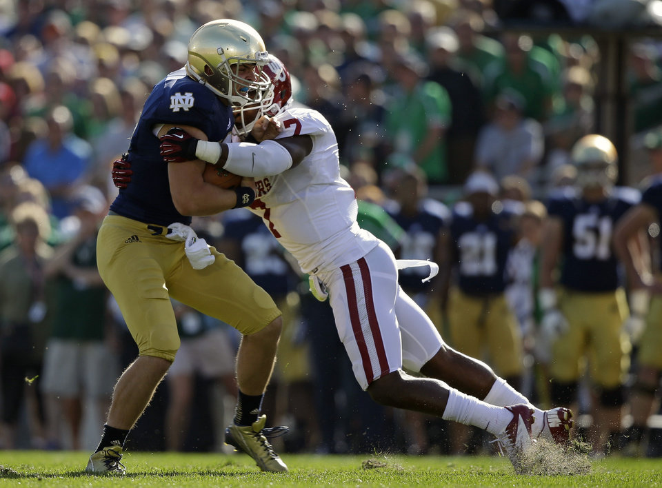 Photo - Notre Dame's Andrew Hendrix, left, is tackled by Oklahoma's Corey Nelson (7) during the first half of an NCAA college football game on Saturday, Sept. 28, 2013, in South Bend, Ind. (AP Photo/Darron Cummings) ORG XMIT: INDC109