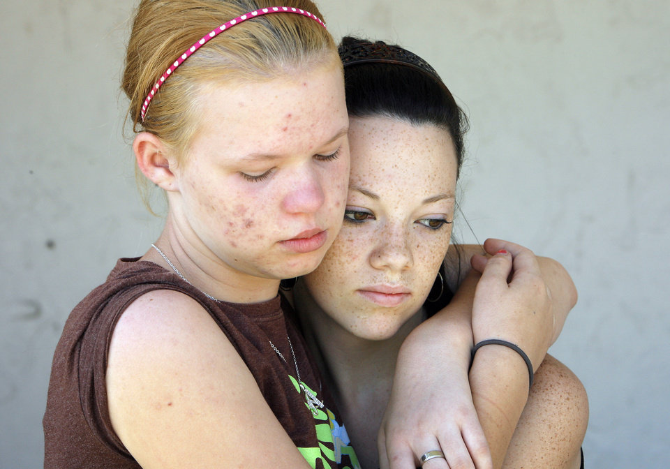 Photo - Junior Amber Shoebottom and senior Tabitha Weaver hug each other at a fundraiser to help the family of Taylor Paschal-Placker and Skyla Whitaker who were shot and killed last Sunday on the dirt road near one of their homes, Tuesday, June 10, 2008.  Photo by David McDaniel /The Oklahoman