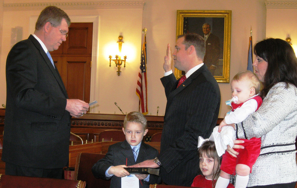 Photo - Above: Rep. Frank Lucas, left, R-Cheyenne, gives the ceremonial oath of office to new Rep. Jim Bridenstine, R-Tulsa, on Thursday on Capitol Hill. Bridenstine was was accompanied by his family. Top: Rep. James Lankford, R-Oklahoma City, delivers the oath to new Rep. Markwayne Mullin, who also was accompanied by his family. PHOTOS BY CHRIS CASTEEL, THE OKLAHOMAN