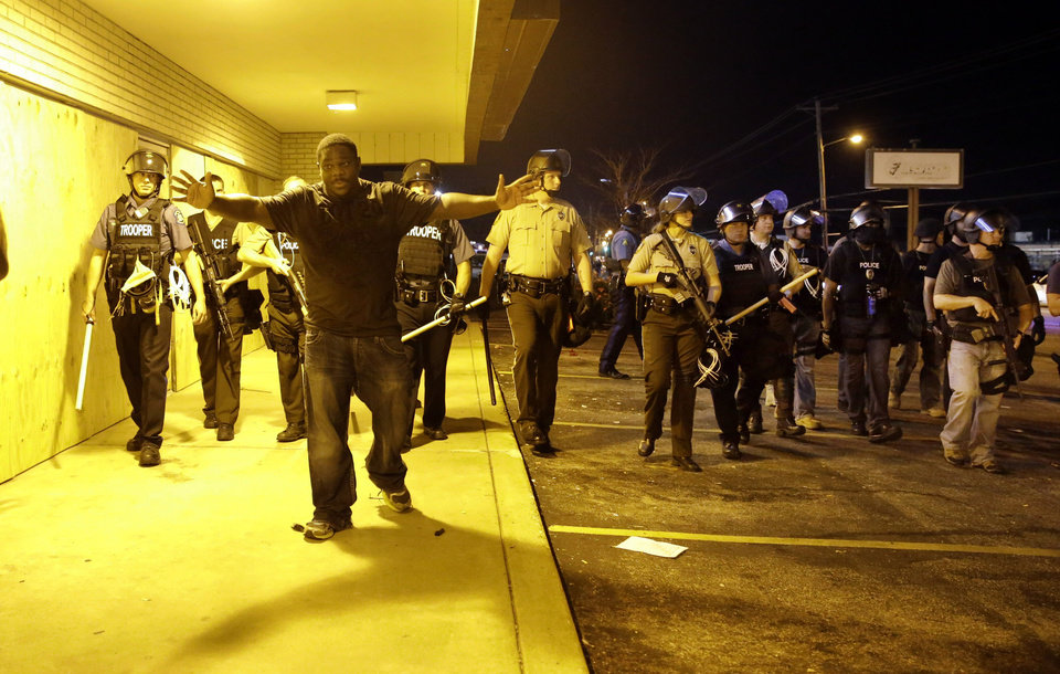 Photo - A community leader tries to get protesters to move back as police attempt to disperse a crowd in Ferguson, Mo. early Wednesday, Aug. 20, 2014. On Saturday, Aug. 9, 2014, a white police officer fatally shot Michael Brown, an unarmed black teenager, in the St. Louis suburb. (AP Photo/Jeff Roberson)