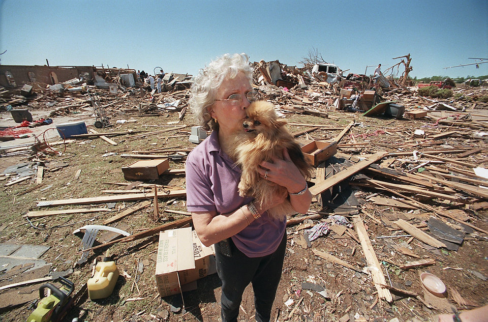 "MAY 3, 1999 TORNADO: France Berisko kisses her dog, ""Baby"", after it was located in storm debris in the Del Aire neighborhood where Berisko's home (in background) was destroyed.  4740 SE 43"