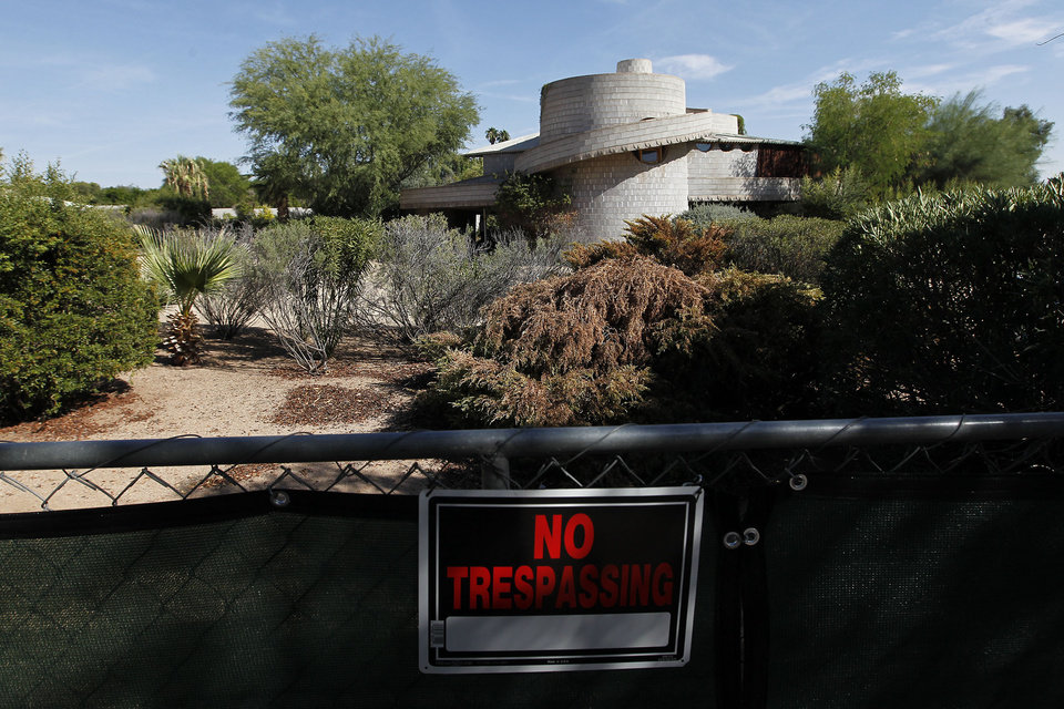 "A ""No Trespassing"" sign hangs on a fence outside a 1952 Frank Lloyd Wright-designed home in the Arcadia neighborhood of Phoenix, Wednesday, Oct. 3, 2012. The city of Phoenix and a developer who was poised to demolish the home have reached an agreement that will put any work on hold while a search continues for a buyer, a city official confirmed Wednesday. (AP Photo/Ross D. Franklin)"