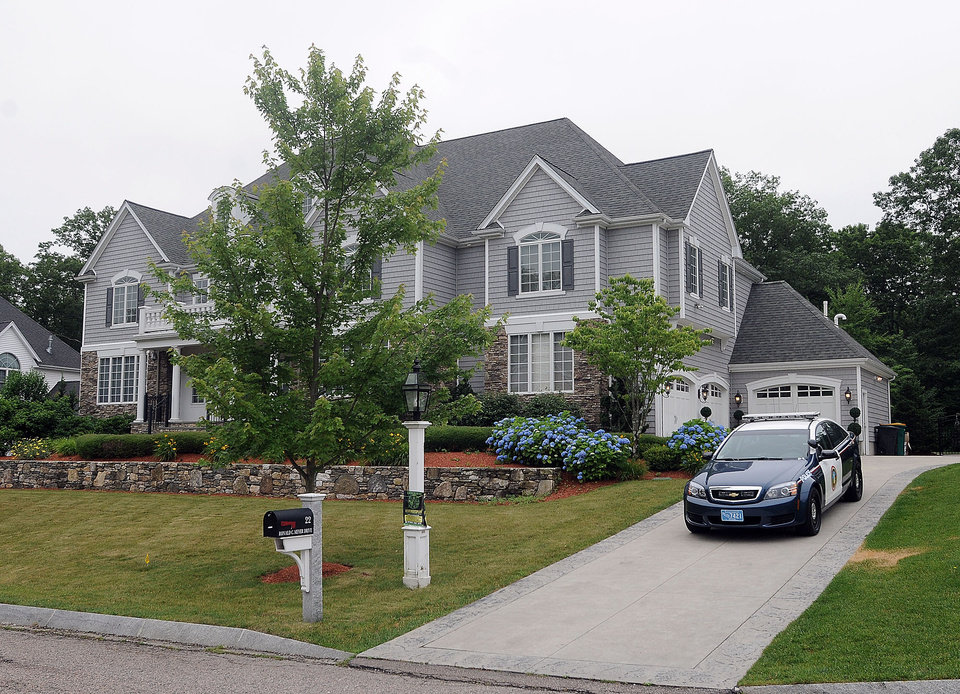 Photo - A police car is parked in the driveway outside the home of former New England Patriots football player Aaron Hernandez Thursday, June 27, 2013, in North Attleboro, Mass.  A judge on Thursday denied bail for the former NFL player, who is charged with first-degree murder in the shooting death of a friend. (AP Photo/The Attleboro Sun Chronicle, Mark Stockwell)  MAGS OUT. MANDATORY CREDIT, PROVIDENCE JOURNAL OUT