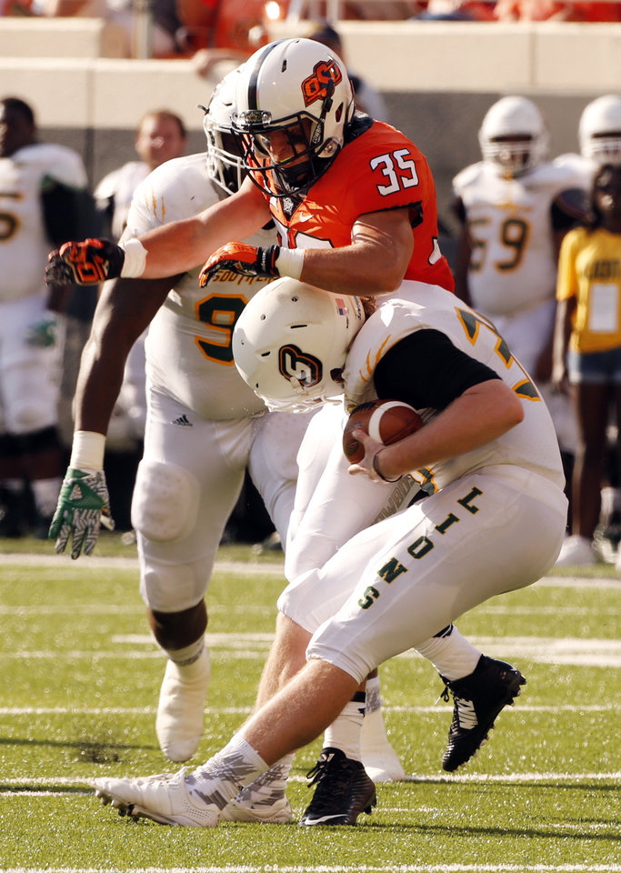 Photo - Oklahoma State's Chance Cook (35) tackles the punter, Jim Speights after a bad snap on fourth down during the second half of a college football game between the Oklahoma State Cowboys (OSU) and the Southeastern Louisiana Lions at Boone Pickens Stadium in Stillwater, Okla., Saturday, Sept. 12, 2015. Photo by Steve Sisney, The Oklahoman