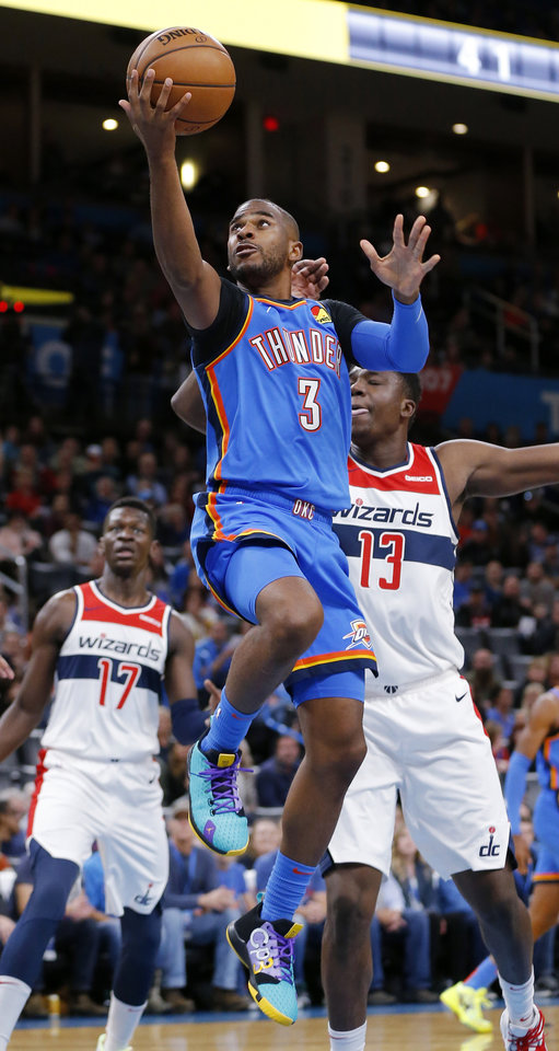 Photo - Oklahoma City's Chris Paul (3) takes the ball to the basket in front of Washington's Thomas Bryant (13) and Isaac Bonga (17) in the first quarter during an NBA basketball game between the Oklahoma City Thunder and the Washington Wizards at Chesapeake Energy Arena in Oklahoma City, Friday, Oct. 25, 2019. [Nate Billings/The Oklahoman]