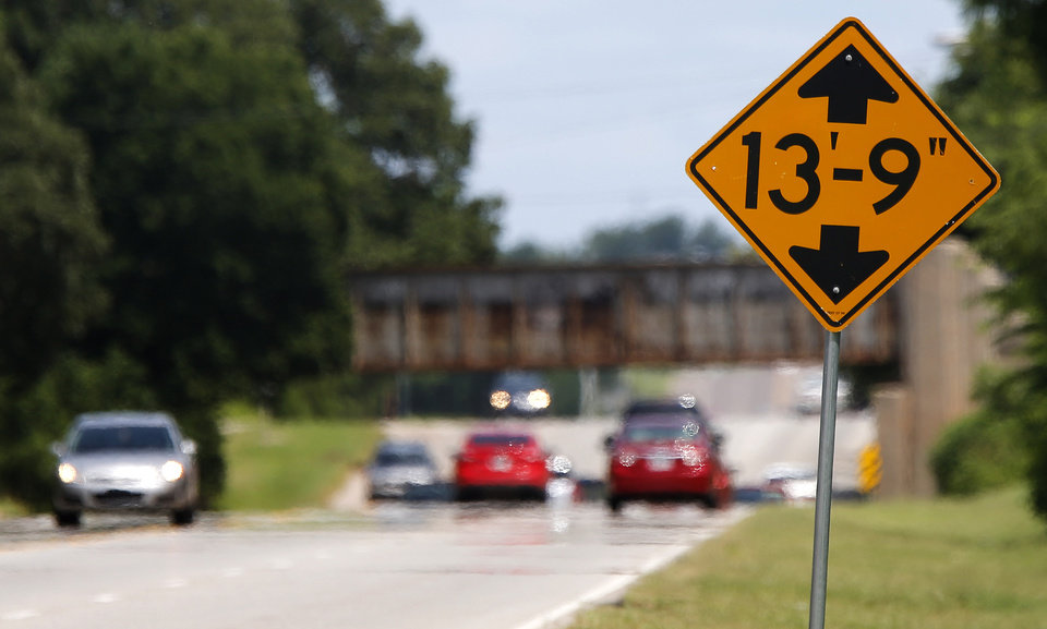 Photo -  A sign warning motorists of a low bridge is seen Friday on NE 23 near Sooner Road. Photo by Bryan Terry, The Oklahoman   BRYAN TERRY -