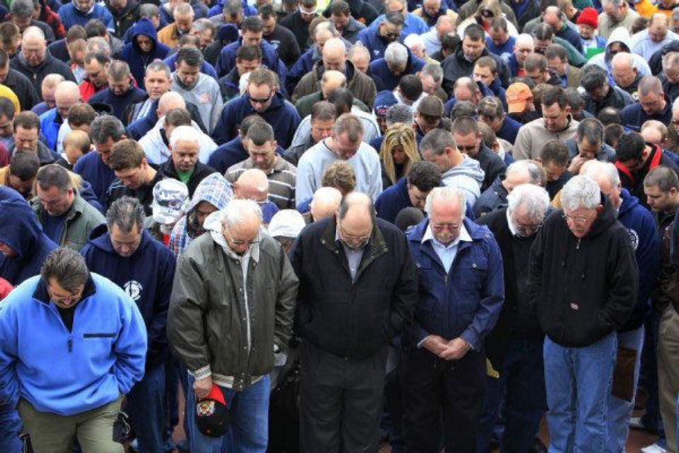 Photo - ORG XMIT: KOD Oklahoma firefighters bow their heads in prayer while they gather during a rally to protest legislation affecting their pension benefits during a rally on the north steps of the state Capitol in Oklahoma City Wednesday, March 9, 2011. Photo by Paul B. Southerland, The Oklahoman