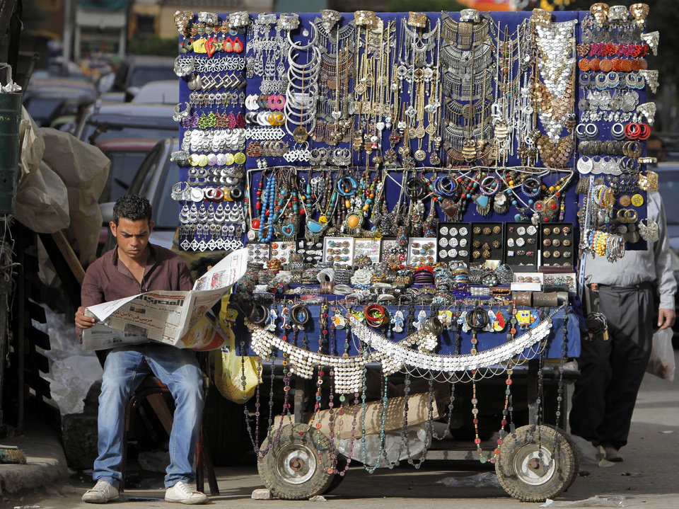 An Egyptian street vendor reads a newspaper while waiting for customers, one of many doing business in an informal economy at a time of high inflation and underemployment, in downtown Cairo, Egypt, Saturday, March 16, 2013. Egypt's multibillion dollar loan request form the International Monetary Fund is considered crucial to freeing up other loans and reassuring foreign investors who abruptly pulled their money out of the country when longtime authoritarian leader Hosni Mubarak was ousted from power in early 2011. (AP Photo/Amr Nabil)