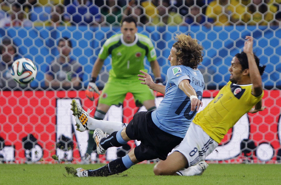 Photo - Uruguay's Diego Forlan, left, is challenged by Colombia's Abel Aguilar as he gets in a shot during the World Cup round of 16 soccer match between Colombia and Uruguay at the Maracana Stadium in Rio de Janeiro, Brazil, Saturday, June 28, 2014. (AP Photo/Sergei Grits)