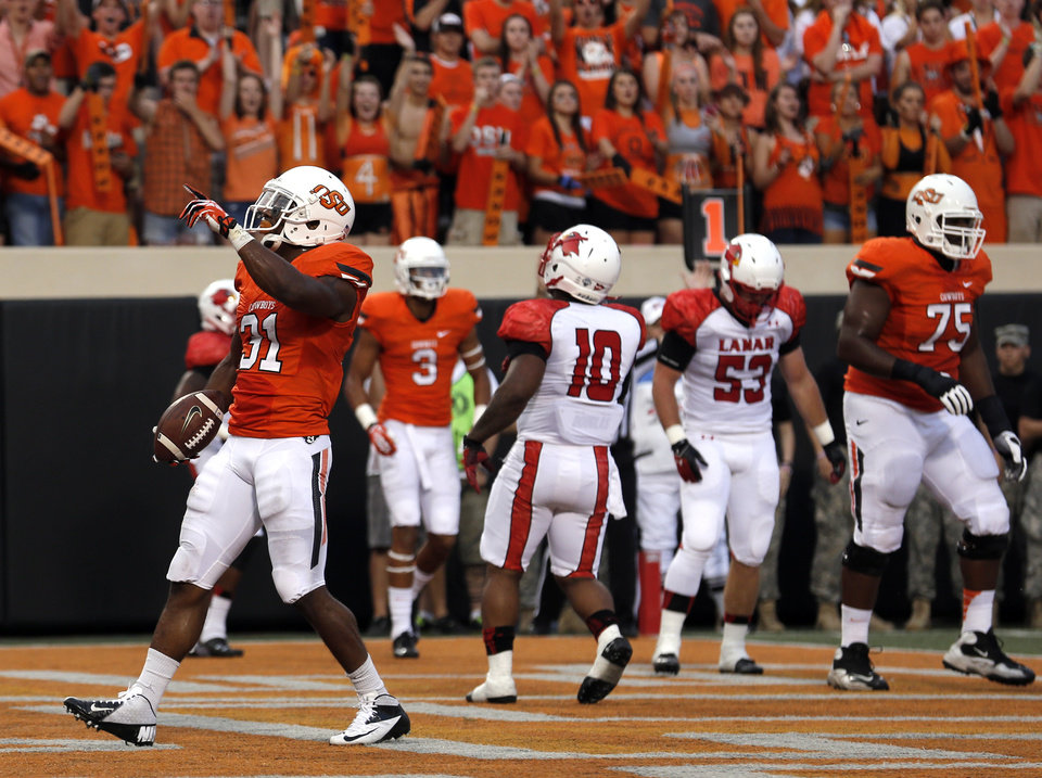 Photo - Oklahoma State's Jeremy Smith (31) celebrates a touchdown during a college football game between the Oklahoma State University Cowboys (OSU) and the Lamar University Cardinals at Boone Pickens Stadium in Stillwater, Okla., Saturday, Sept. 14, 2013. Photo by Sarah Phipps, The Oklahoman