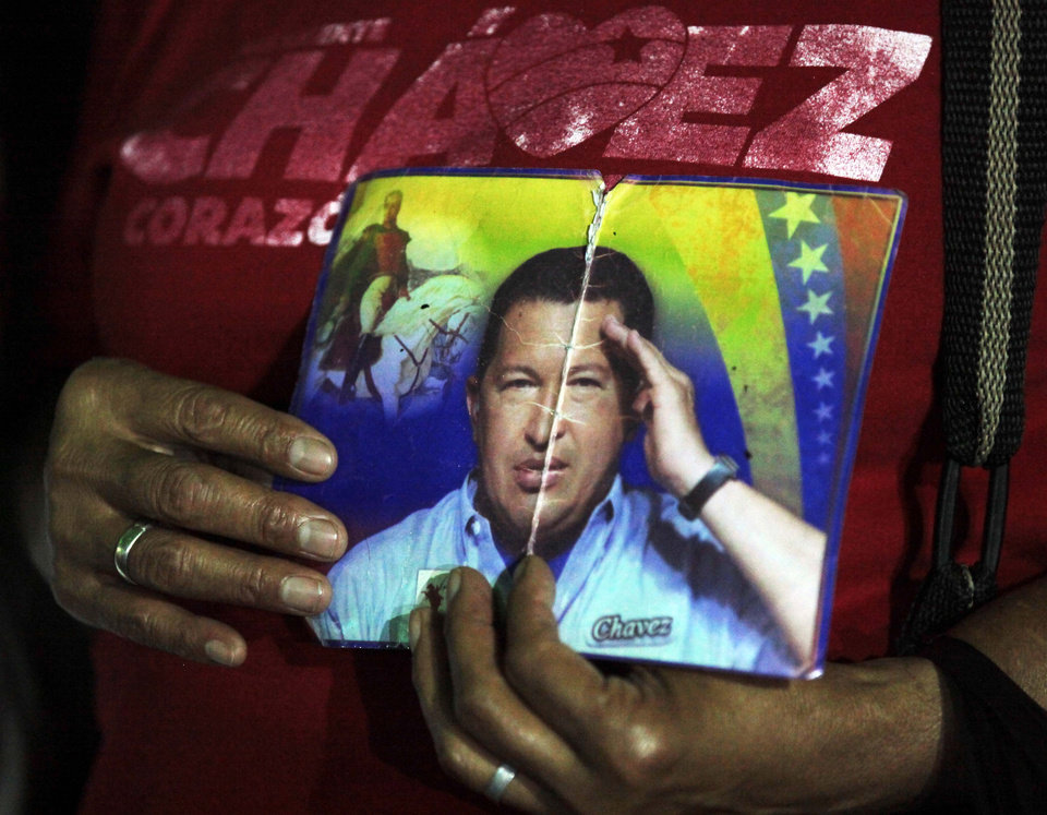 A person holds up images of Venezuela's President Hugo, right, and Venezuela's independence hero Simon Bolivar as people gather to pray for Chavez at Simon Bolivar square in Caracas, Venezuela, Tuesday, Dec. 11, 2012. Doctors began operating on Chavez  in Cuba, his government said, after his cancer reappeared despite a year and a half of surgeries and treatments. (AP Photo/Fernando Llano)