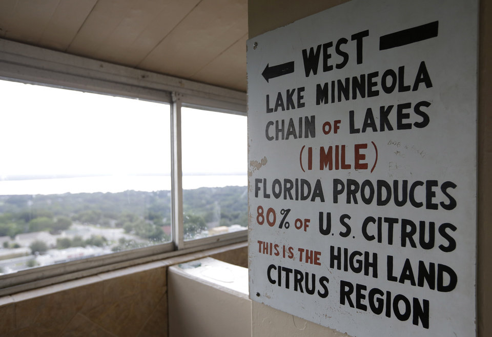 Photo - In this Friday, July 25, 2014 photo, a sign in the Florida Citrus Tower points west to Florida's citrus growing region, in Clermont, Fla. The observation tower was built in 1956 as a tourist attraction to view miles of citrus groves. Today Florida's $9 billion citrus industry is facing its biggest threat yet by a tiny invasive bug called the Asian Citrus Psyllid, which carries bacteria that are left behind when the psyllid feeds on a citrus tree's leaves. Eventually disease clogs the tree's vascular system and the tree slowly dies. (AP Photo/Lynne Sladky