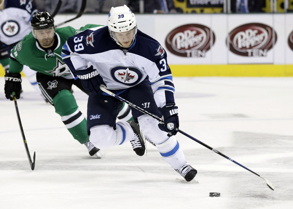 Photo - Winnipeg Jets' Tobias Enstrom (39), of Sweden, controls the puck as Dallas Stars center Vernon Fiddler (38) gives chase in the first period of an NHL hockey game, Saturday, Oct. 26, 2013, in Dallas. (AP Photo/Tony Gutierrez)