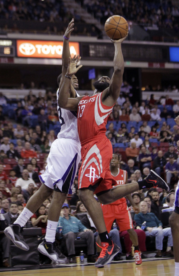 Houston Rockets guard James Harden, right, goes to the basket against   Sacramento Kings guard Marcus Thornton during the first quarter of an NBA basketball game in Sacramento, Calif., Sunday, Feb. 10, 2013.(AP Photo/Rich Pedroncelli)