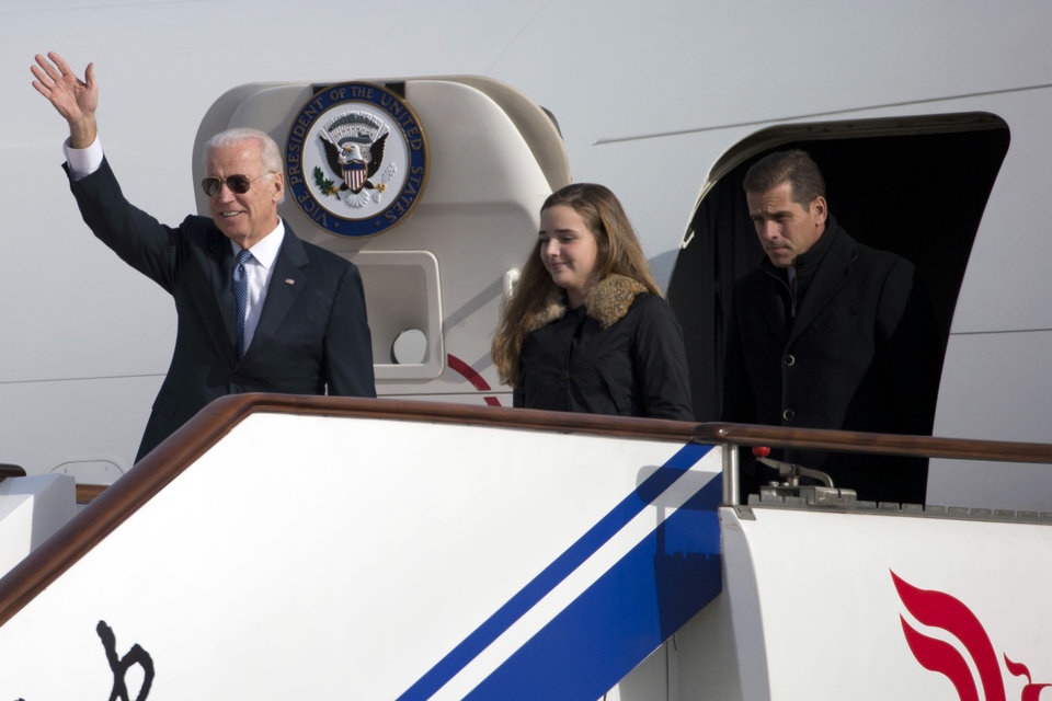 Photo - FILE - This Dec. 4, 2013, file photo shows U.S. Vice President Joe Biden, left, arriving on Air Force Two in Beijing, China, with his son Hunter Biden, right, and his granddaughter Finnegan Biden. As the Vice President travels to Ukraine Saturday, June 7, 2014, his youngest son, Hunter, 44, has been hired by a private Ukrainian company that promotes energy independence from Russia, but is commercially active in the breakaway Russian-backed state of Crimea and owned by a former government minister with ties to Ukraine's ousted pro-Russian president. (AP Photo/Ng Han Guan, Pool)