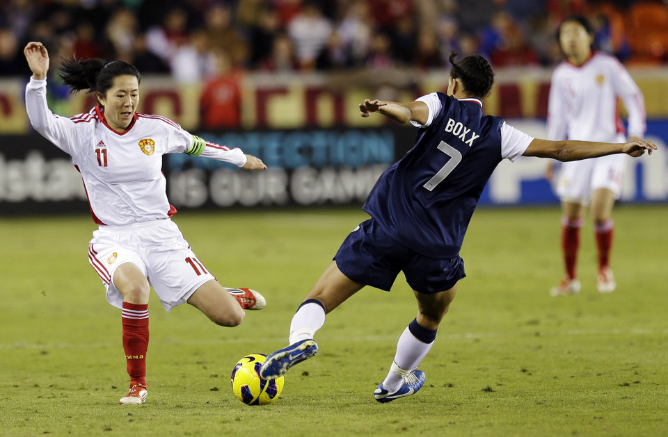 United States\' Shannon Boxx (7) and China\'s Pu Wei go after the ball during the second half of an exhibition soccer match, Wednesday, Dec. 12, 2012, in Houston. (AP Photo/David J. Phillip)