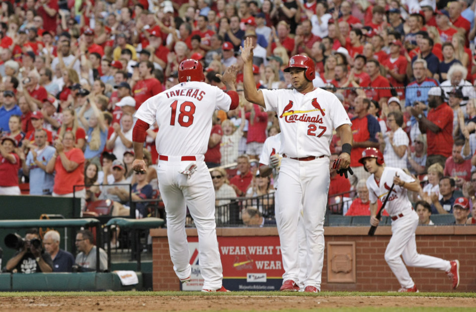 Photo - St. Louis Cardinals' Oscar Taveras (18) celebrates with teammate Jhonny Peralta (27) after they both scored on a two-RBI double by Kolten Wong in the second inning of a baseball game against the Pittsburgh Pirates, Tuesday, July 8, 2014 in St. Louis. (AP Photo/Tom Gannam)