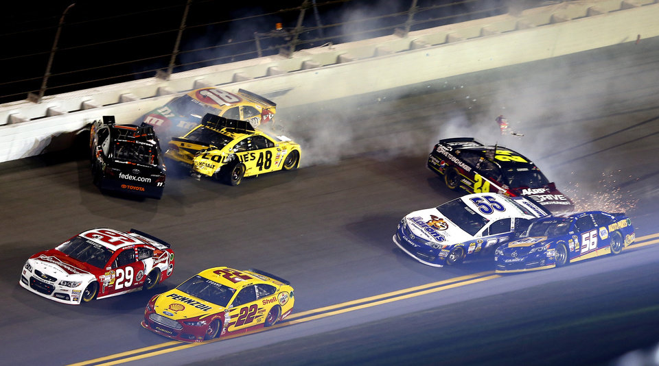 Photo - Kevin Harvick (29) and Joey Logano (22) drive away from a wreck involving Denny Hamlin, top left, Jimmie Johnson (48), Kyle Busch (18), Jeff Gordon (24) and Mark Martin (55) in the NASCAR Sprint Unlimited auto race at Daytona International Speedway, Saturday, Feb. 16, 2013, in Daytona Beach, Fla. Marin Truex (56) was able to clear the wreck and continue in the race. (AP Photo/John Moore)